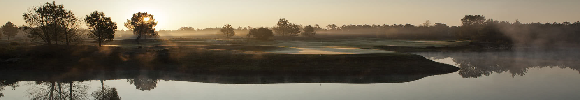 Golf course in the morning with mist and a Sunrise